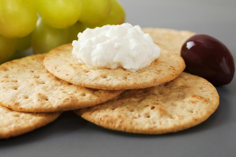 Cottage Cheese with Crackers. Grapes and olives on a dark platter stock image