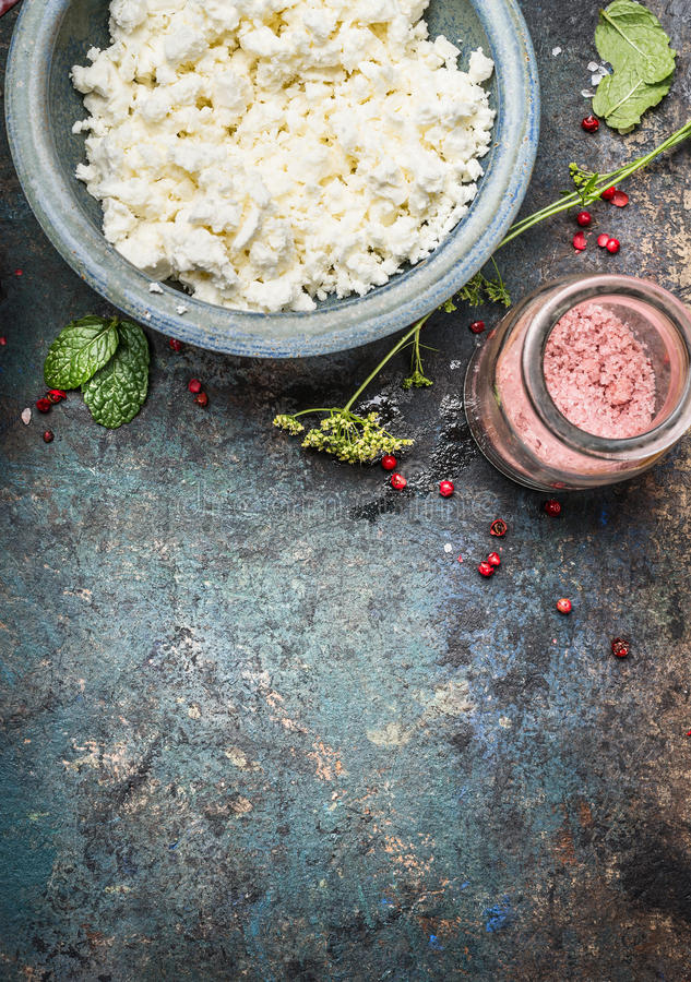 Cottage cheese or Feta cheese in blue bowl with fresh seasoning and salt on dark rustic background, top view stock photography