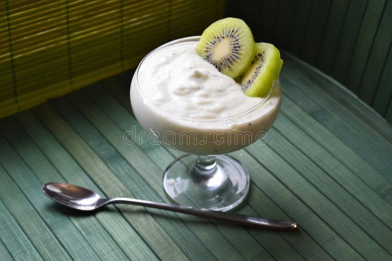 Cottage cheese with kiwi puree in a glass bowl stock photography