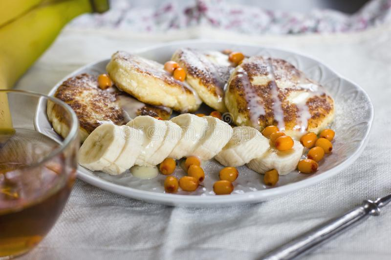 Cottage cheese pancakes with banana slices and sea buckthorn berries. Healthy breakfast. View from top stock image