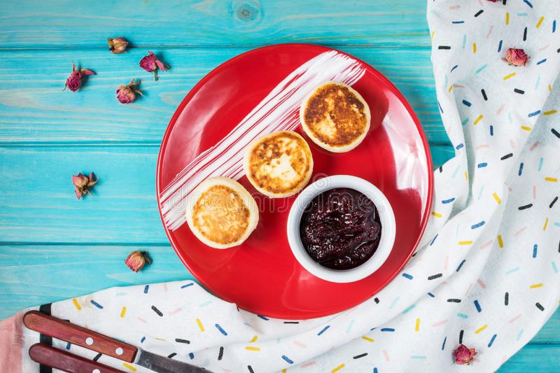 Cottage cheese pancakes on blue wooden background. Syrniki with jam. Homemade food royalty free stock image