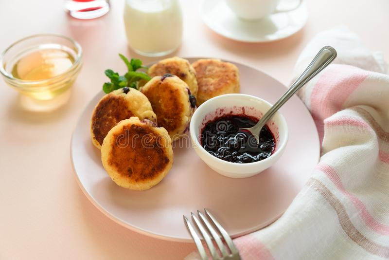Cottage cheese pancakes with blueberry, honey, jam and coffee. Ukrainian syrniki, cottage cheese fritters or pancakes on pink royalty free stock images