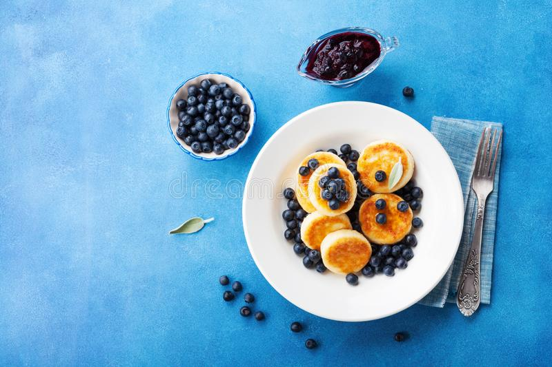 Cottage cheese pancakes or curd fritters decorated honey and blueberry in plate on blue table top view. Healthy and diet breakfast stock photo