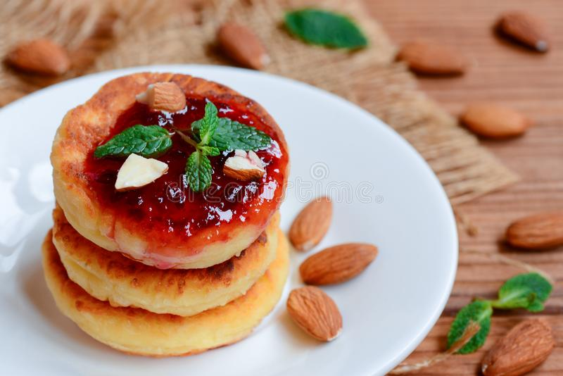 Cottage cheese pancakes. Fried cottage cheese pancakes with berry jam and almonds on a white plate. Traditional russian syrniki royalty free stock photo