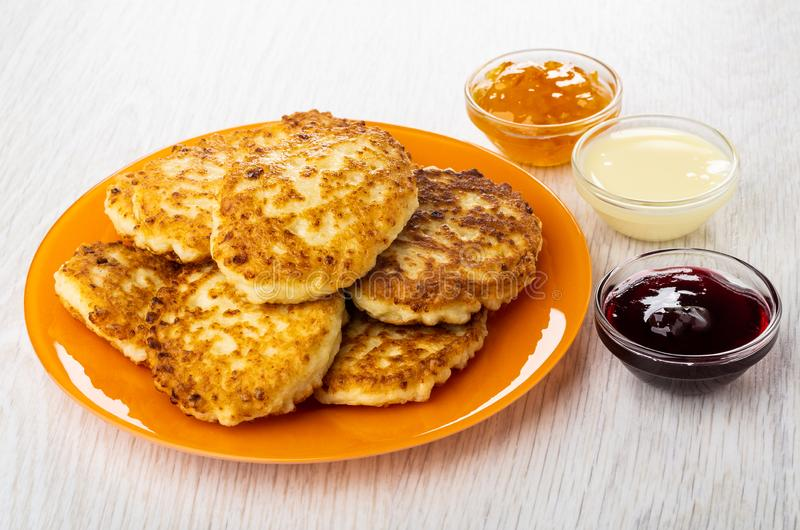 Cottage cheese pancakes in plate, bowls with orange jam, condensed milk, cherry jam on table stock images