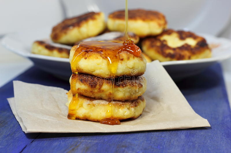 Cottage cheese pancakes with honey. Stack of cheesecakes smeared with honey. soft focus stock images