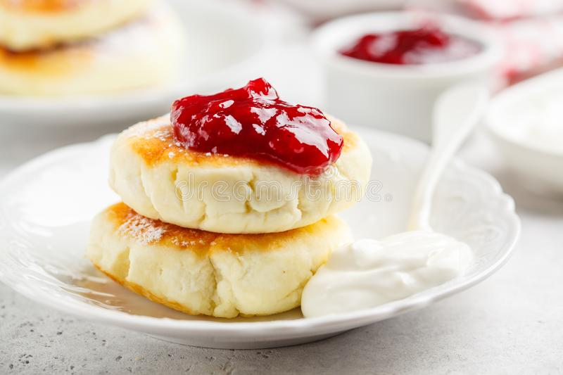 Cottage cheese pancakes with sour cream and jam on white plate stock image