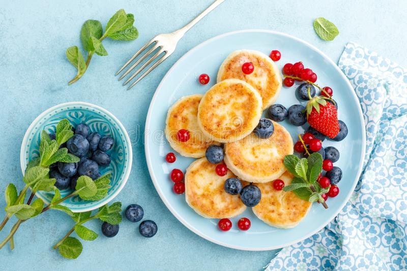 Cottage cheese pancakes, syrniki with fresh berries for breakfast royalty free stock photo