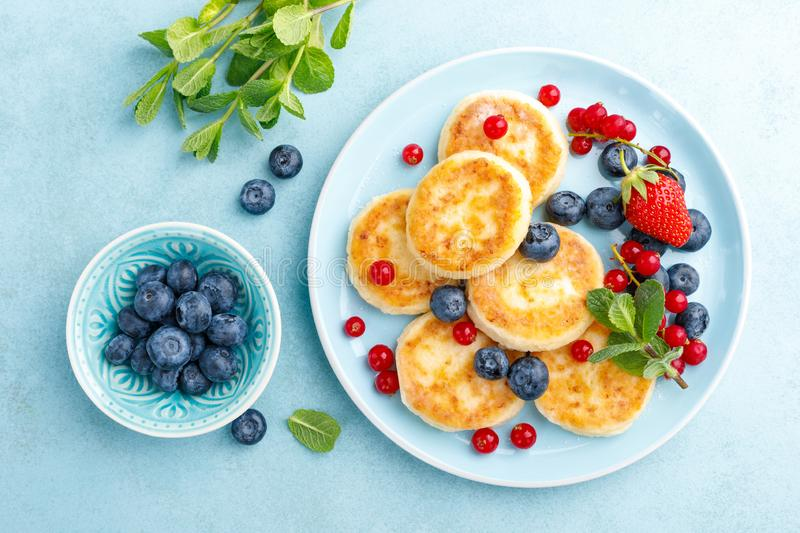 Cottage cheese pancakes, syrniki with fresh berries for breakfast stock photo