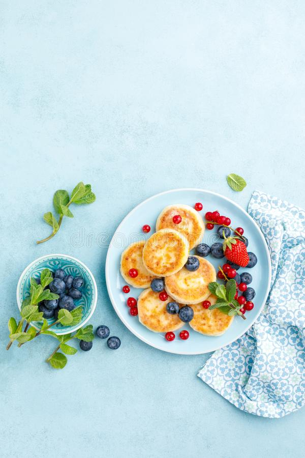 Cottage cheese pancakes, syrniki with fresh berries for breakfast stock image