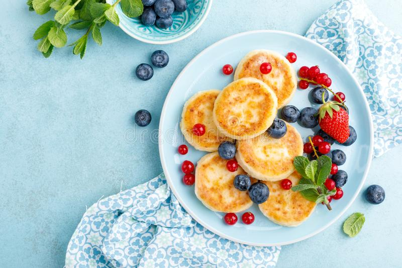 Cottage cheese pancakes, syrniki with fresh berries for breakfast royalty free stock image