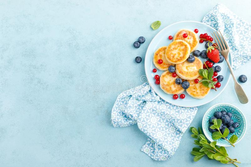 Cottage cheese pancakes, syrniki with fresh berries for breakfast royalty free stock images
