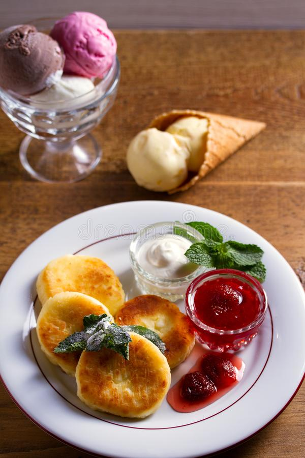 Cottage cheese pancakes. Syrniki with fresh mint, sour cream and strawberry jam, ice cream - dessert concept. stock images