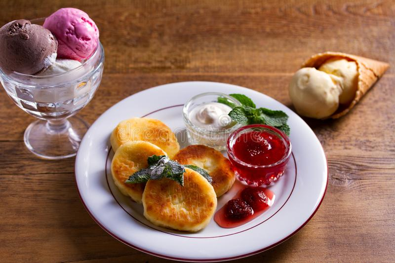 Cottage cheese pancakes. Syrniki with fresh mint, sour cream and strawberry jam, ice cream - dessert concept. Cottage cheese pancakes. Syrniki with fresh mint stock image