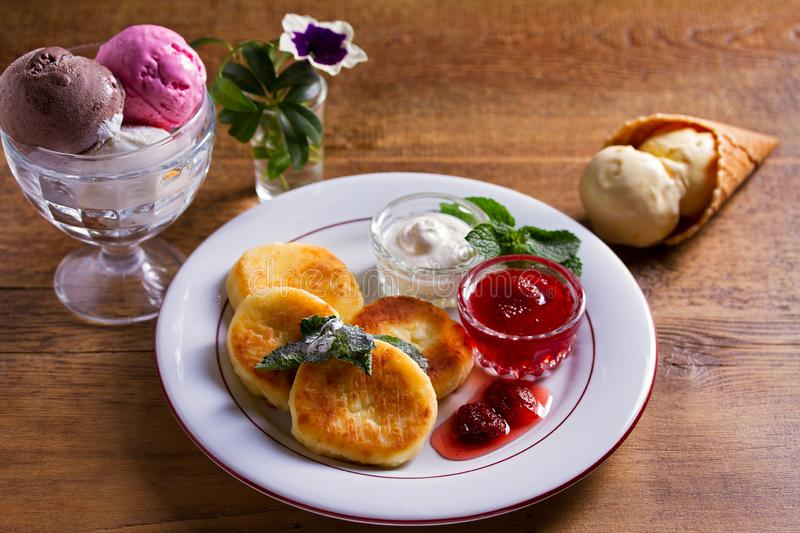 Cottage cheese pancakes. Syrniki with fresh mint, sour cream and strawberry jam, ice cream - dessert concept. Cottage cheese pancakes. Syrniki with fresh mint royalty free stock images