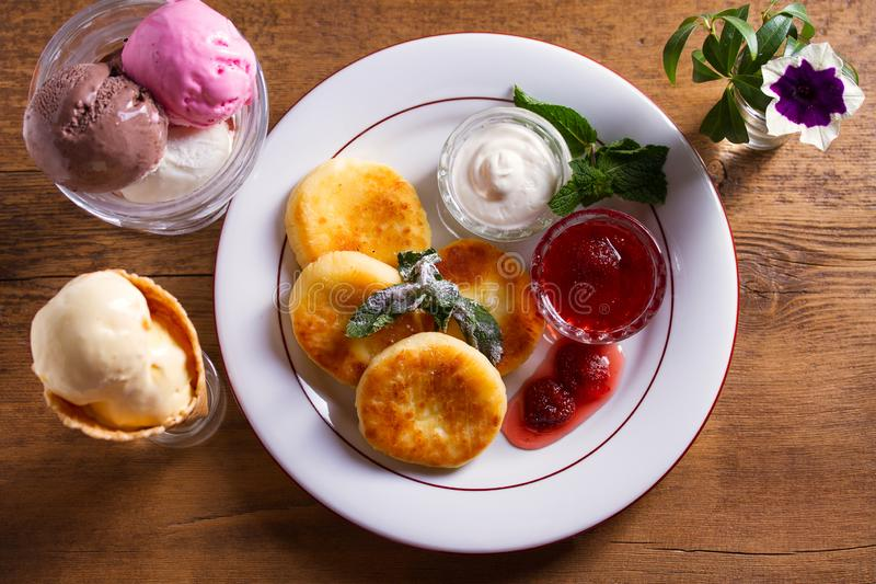 Cottage cheese pancakes. Syrniki with fresh mint, sour cream and strawberry jam, ice cream - dessert concept. View from above, top studio shot royalty free stock images