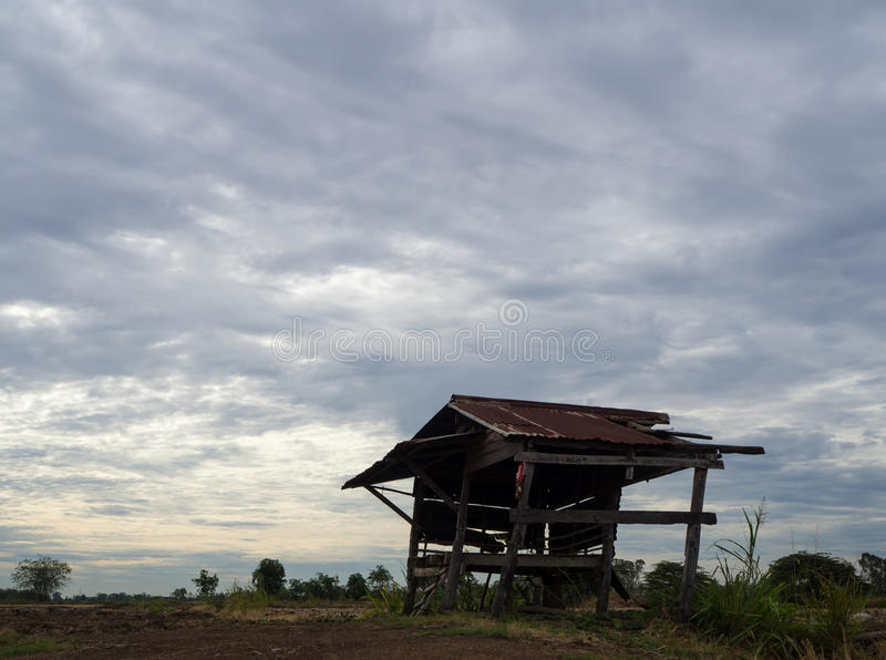 Cottage with cloudy. Zinc Old wooden hut on the barren ground in agriculture, which is a cloudy scene royalty free stock image
