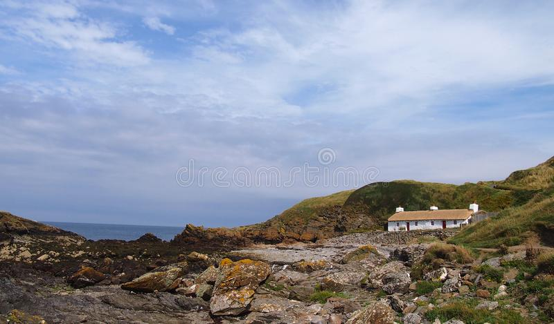 Cottage couvert de chaume chez Niarbyl sur l'île de Man images stock