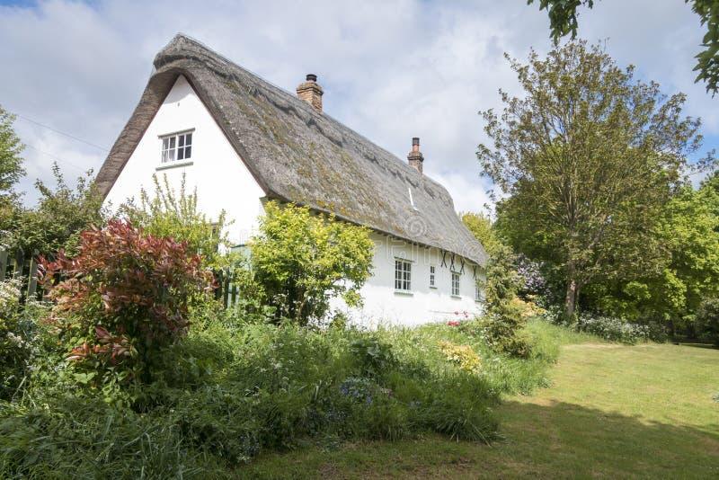 Cottage couvert de chaume dans un village anglais photos libres de droits