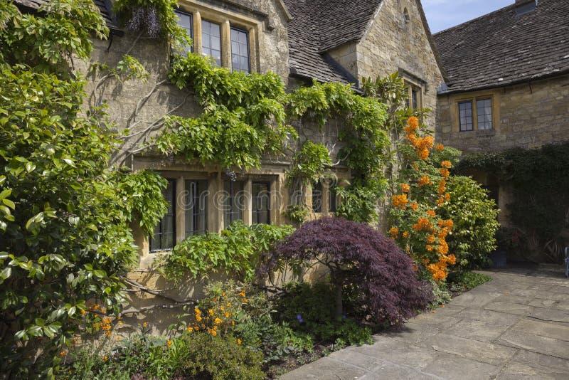 Cottage de Cotswold avec la jolie frontière de fleur, Angleterre photographie stock
