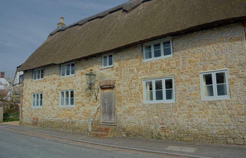 Cottage de grès avec le toit couvert de chaume image libre de droits