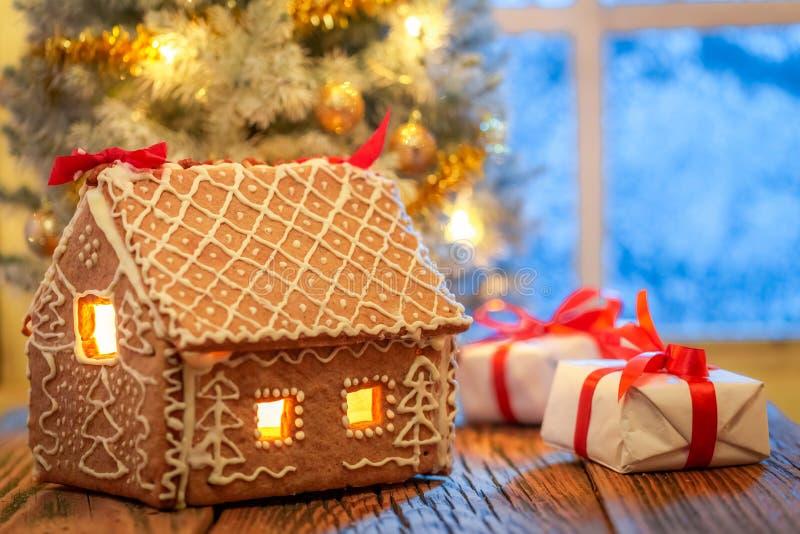 Cottage de pain d'épice, présents et arbre de Noël avec la fenêtre congelée image libre de droits