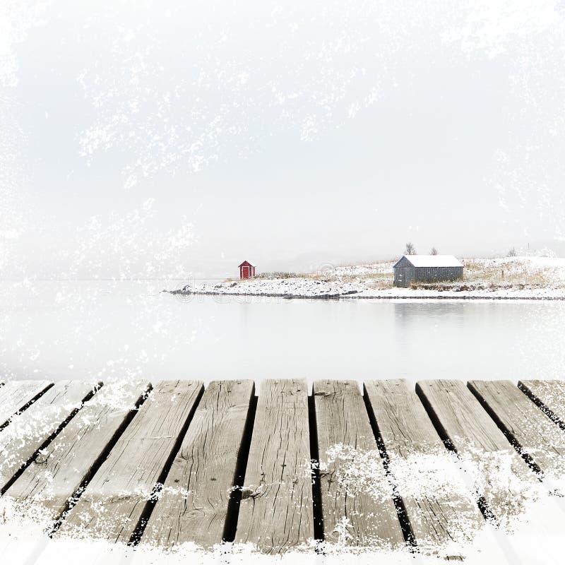 Cottage della Norvegia sulla costa di inverno con il bacino di legno della piattaforma con il lerciume bianco della neve immagine stock