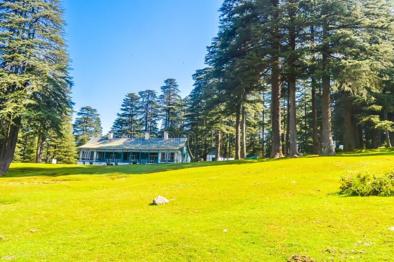 Cottage di concetto di vacanze estive circondato con gli alberi verdi e l'erba verde vicino al parco pubblico con il cielo blu-ch fotografia stock