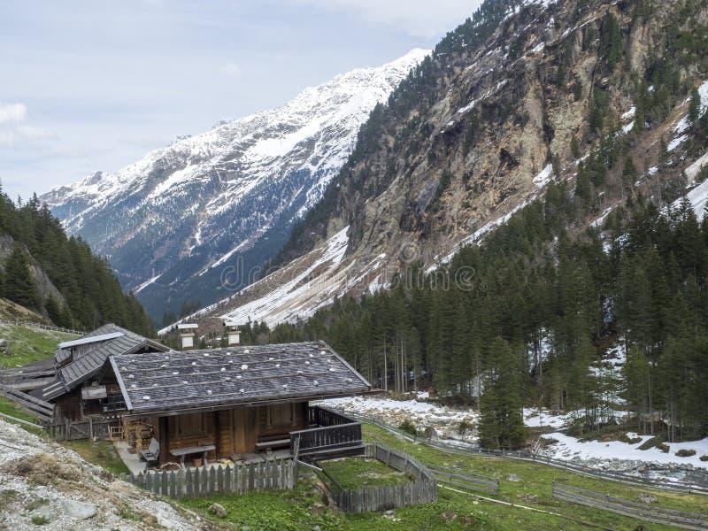 Cottage di legno alpino vicino alla cascata del ghiacciaio di GRAWA situata in valle di Stubai, Tirolo, Austria Fiume della monta immagini stock libere da diritti
