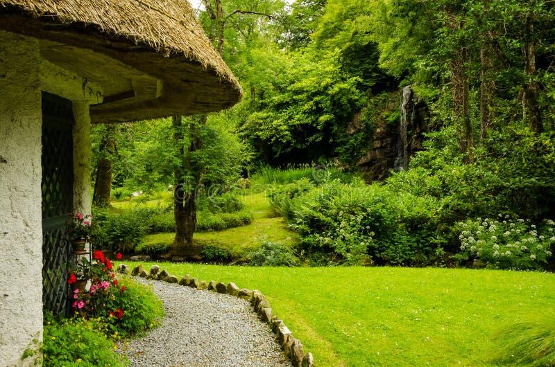 Cottage e cascata ricoperti di paglia fotografie stock