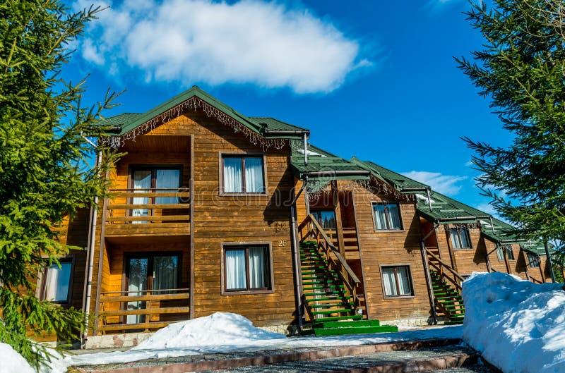 Cottage en bois parmi le logement confortable de forêt de pin dans la station de sports d'hiver Bukovel image libre de droits