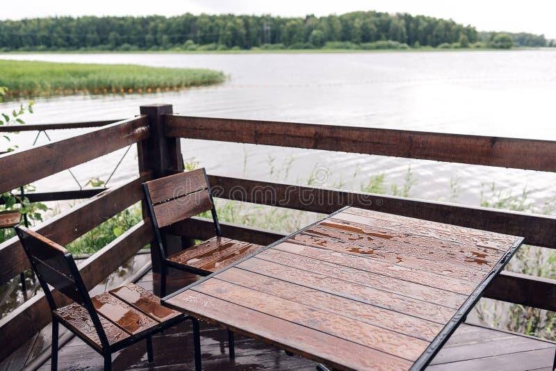 Cottage in foresta vicino al fiume con il grande terrazzo di legno Camera sull'acqua nel lago, una bella banca Posto ideale per fotografia stock libera da diritti