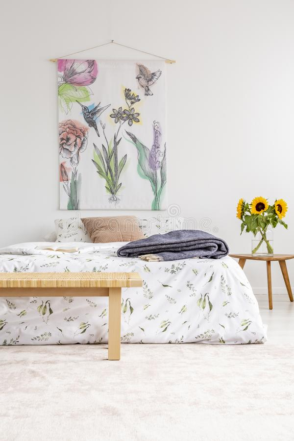 Cottage house minimal bedroom interior with colorful flowers and birds painted on fabric above a bed which is dressed in natural t. Extile sheets. Sunflowers by royalty free stock image