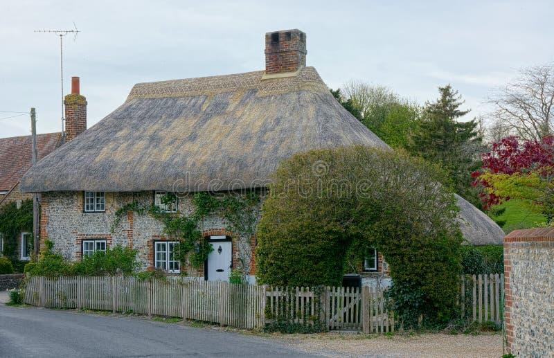 Cottage idilliaco con il tetto ricoperto di paglia in villaggio rurale, Regno Unito immagini stock
