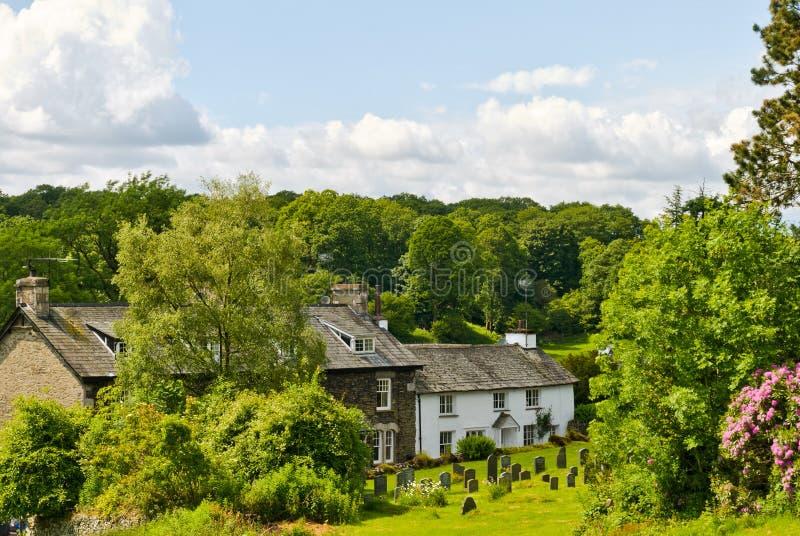 Cottage imbiancato nella regolazione del terreno boscoso. immagini stock libere da diritti