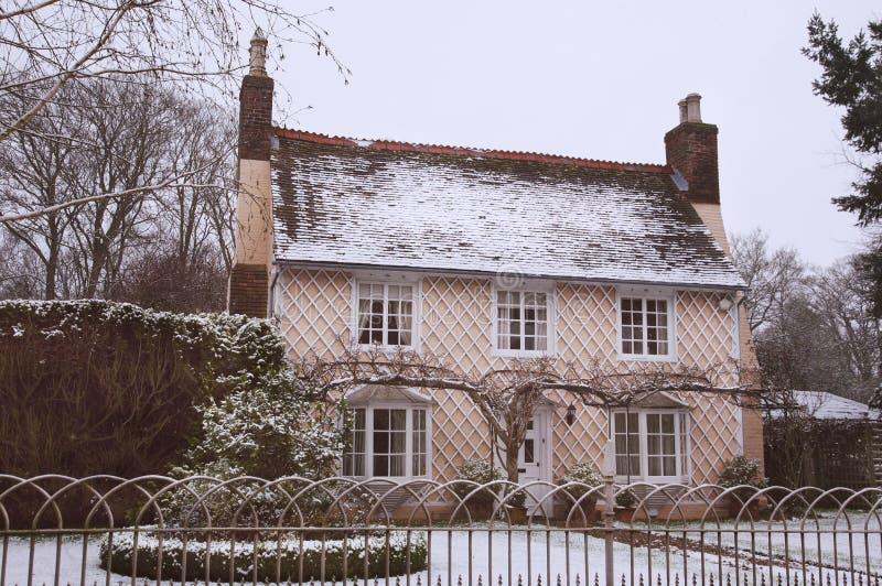 Cottage inglese del paese nella neve di inverno immagine stock