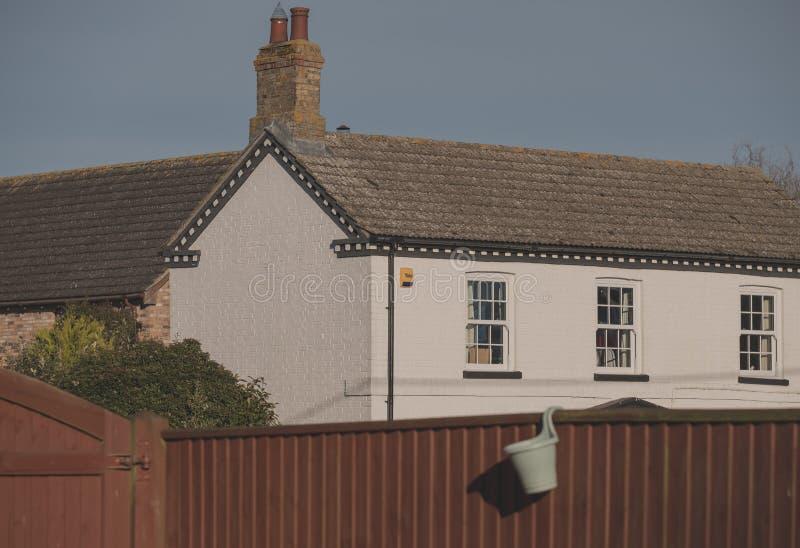 Cottage isolé anglais typiquement dénommé vu des confins de la propriété semblable voisine de Na images stock