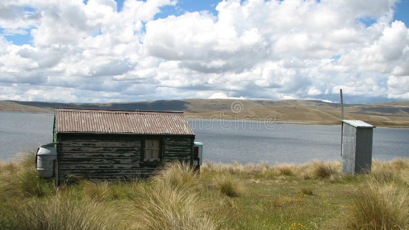Cottage on lakeside. This old crib/cottage or bach is still used as a place to get away from busy life and back to basic living. Even a long drop toilet away stock photos
