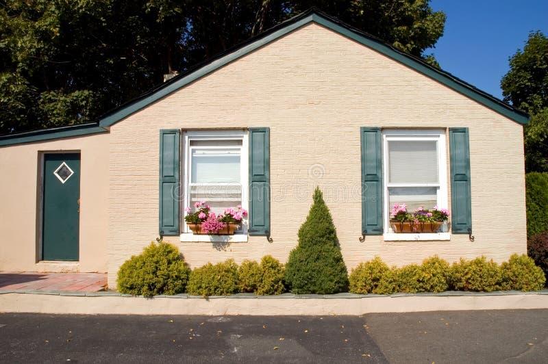 Cottage molto piccolo con i contenitori di fiore fotografia stock