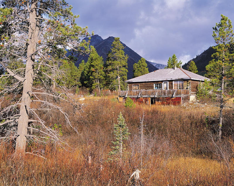 Cottage and mountains. Abandoned city of Cassiar in British Columbia royalty free stock photo