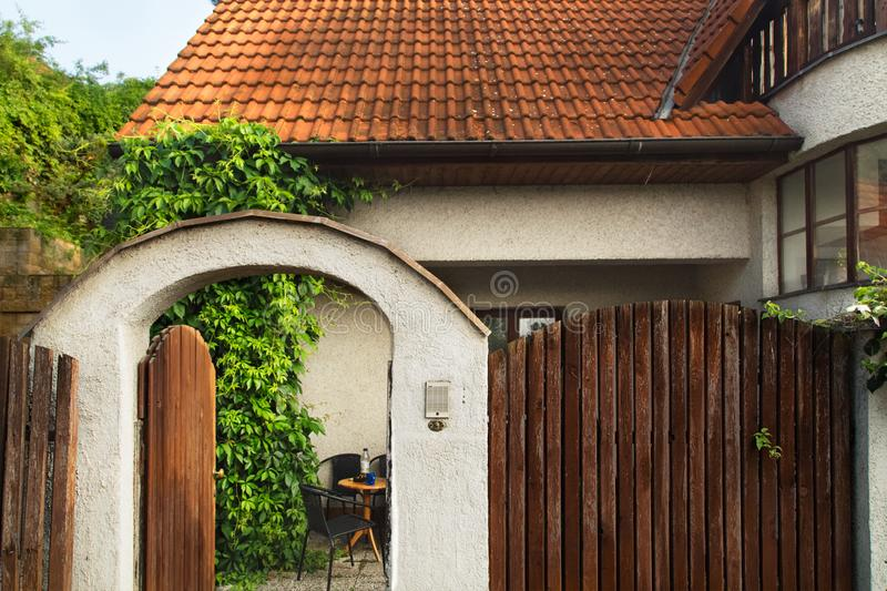 Cottage red roof house with garden wooden wicket.  Opened wooden gate. stock photography
