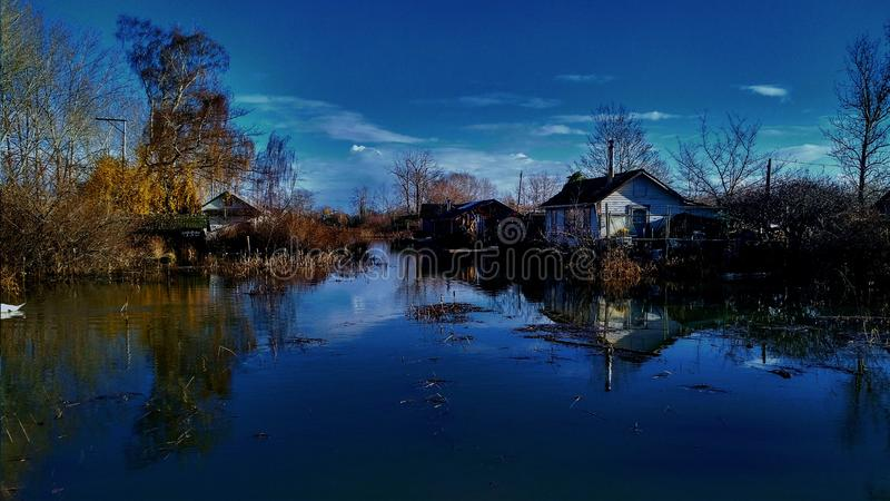 Cottage on the river. Sun going down on a fall evening, heritage site near Steveston British Columbia, at Richmond, Finn Slough. Beautiful rustic  cottage house royalty free stock photo