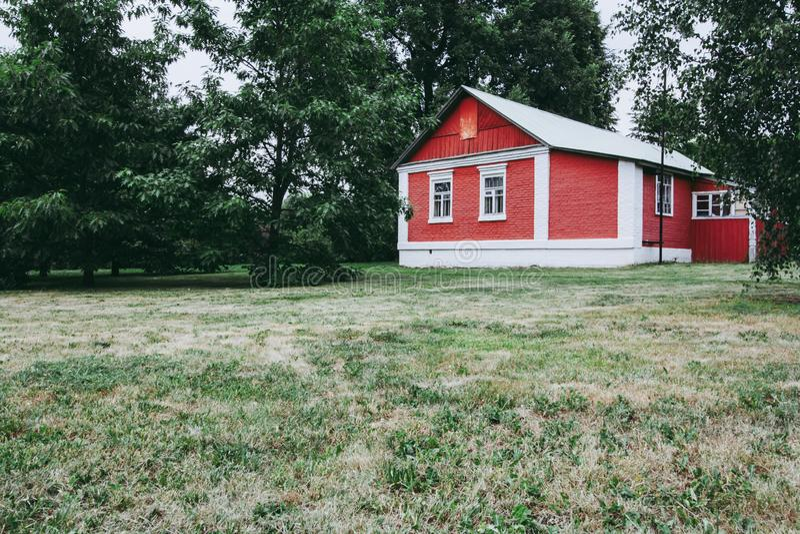 Cottage rosso della casa con mattoni a vista nel legno fotografia stock