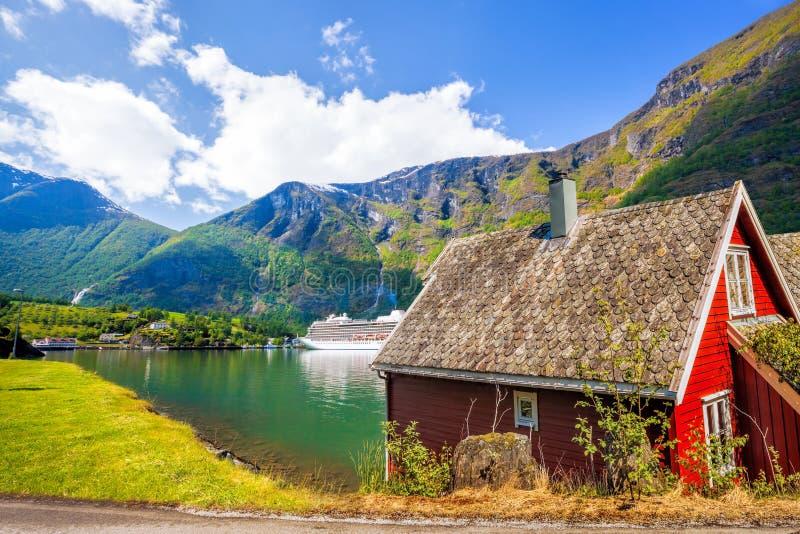 Cottage rouge contre le bateau de croisière dans le fjord, Flam, Norvège image stock