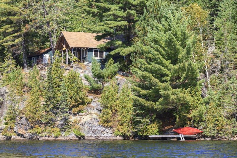Cottage sul lago canoe fotografia stock libera da diritti