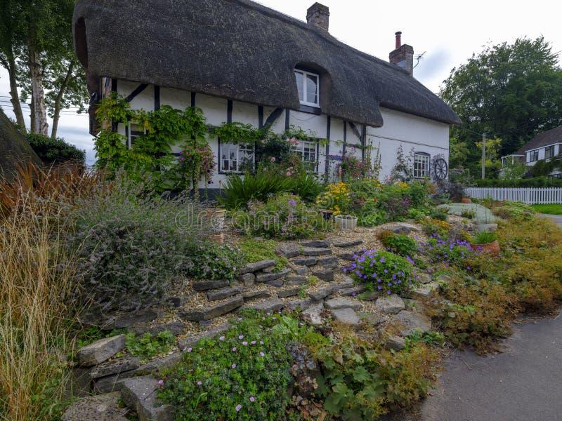 Cottage tipico del paese del Hampshire - metà armata in legno e ricoperta di paglia - con il giardino abbastanza anteriore nel vi fotografie stock libere da diritti
