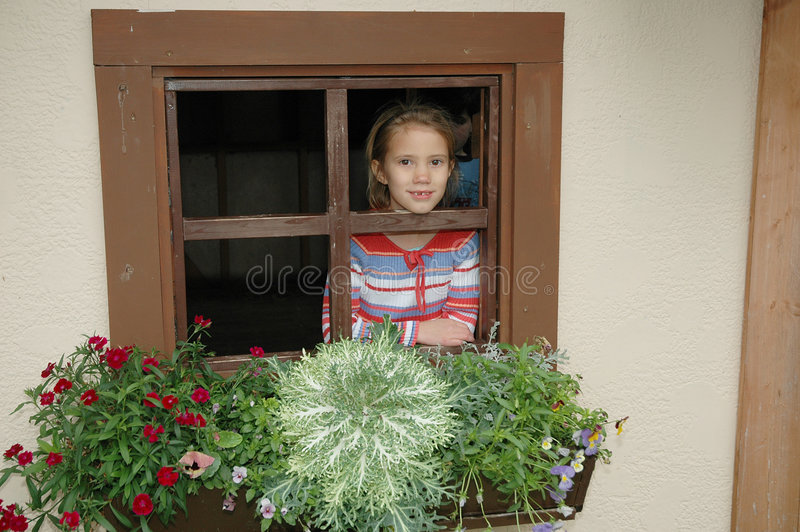 Cottage Window 2. Little girl looks out a window stock photo