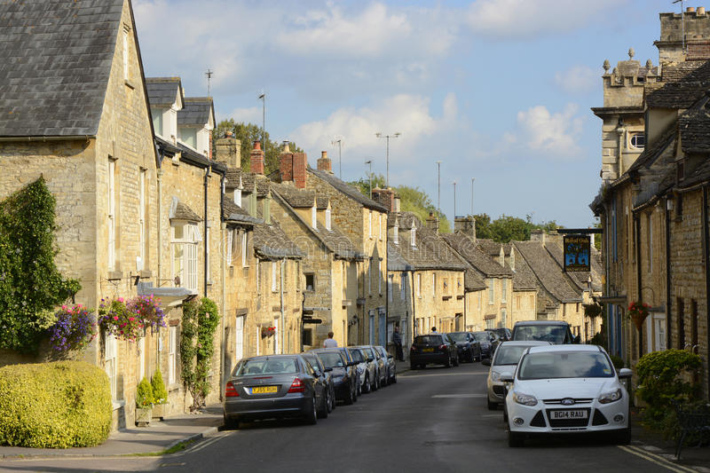 Cottages in Burford, Oxfordshire, England. Old Cotswold Stone cottages in Burford in Oxfordshire, England. With parked cars and people royalty free stock photo