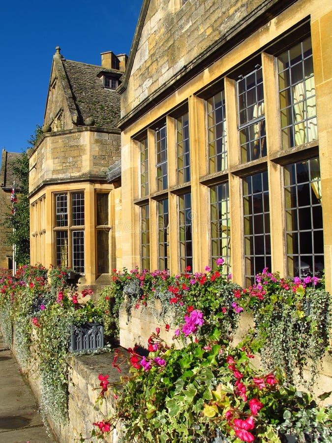 Cottages de village de Cotswolds Angleterre Broadway avec des boîtes de fleur photographie stock libre de droits