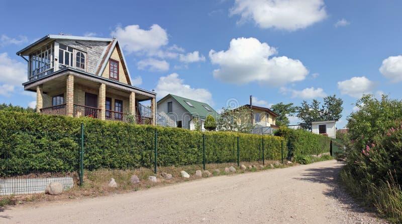 Cottages rustiques de style derrière une barrière verte photographie stock libre de droits